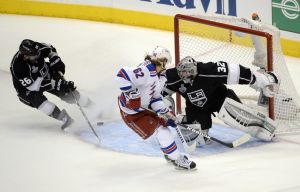 Jun 4, 2014; Los Angeles, CA, USA; New York Rangers left wing Carl Hagelin (62) scores a goal past Los Angeles Kings goalie Jonathan Quick (32) and defenseman Slava Voynov (26) in the first period during game one of the 2014 Stanley Cup Final at Staples Center. Mandatory Credit: Richard Mackson-USA TODAY Sports