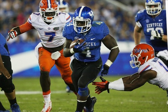 Sep 28, 2013; Lexington, KY, USA; Kentucky Wildcats running back Raymond Sanders (4) runs the ball against Florida Gators linebacker Ronald Powell (7) at Commonwealth Stadium. Mandatory Credit: Mark Zerof-USA TODAY Sports