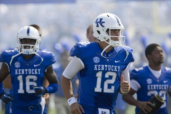 Sep 7, 2013; Lexington, KY, USA; Kentucky Wildcats quarterback Reese Phillips(12) and cornerback Cody Quinn(16) come out on the field during the game against the Miami (Oh) Redhawks at Commonwealth Stadium. Mandatory Credit: Mark Zerof-USA TODAY Sports