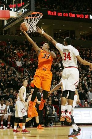 Feb 8, 2014; Lubbock, TX, USA; Oklahoma State Cowboys guard Marcus Smart (33) scores on a layup against Texas Tech Red Raiders forward Alex Foster (34) at United Spirit Arena. Mandatory Credit: Michael C. Johnson-USA TODAY Sports