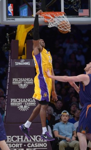 Dec 10, 2013; Los Angeles, CA, USA; Los Angeles Lakers guard Kobe Bryant (24) dunks the ball over Phoenix Suns center Miles Plumlee (22) at Staples Center. Mandatory Credit: Kirby Lee-USA TODAY Sports