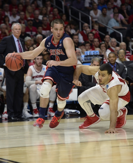 Mar 28, 2015; Los Angeles, CA, USA; Arizona Wildcats guard T.J. McConnell (4) moves the ball ahead of Wisconsin Badgers guard Traevon Jackson (12) during the first half in the finals of the west regional of the 2015 NCAA Tournament at Staples Center. Mandatory Credit: Robert Hanashiro-USA TODAY Sports