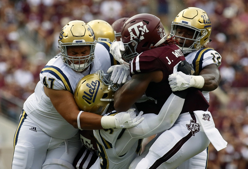 Sep 3, 2016; College Station, TX, USA; Texas A&M Aggies running back James White (20) is tackled by defensive lineman Eddie Vanderdoes (47) and defensive lineman Takkarist McKinley (98) and linebacker Jayon Brown (12) during the first quarter at Kyle Field. Mandatory Credit: Ray Carlin-USA TODAY Sports