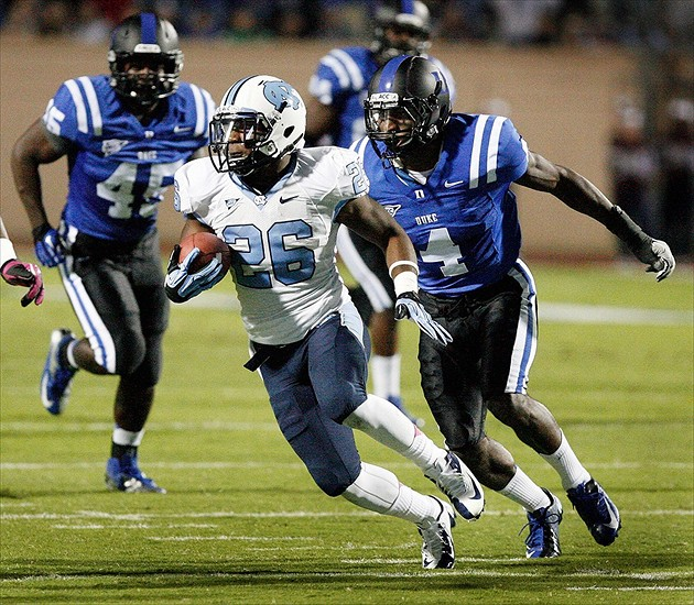 Oct 20, 2012; Durham, NC, USA; North Carolina Tar Heels running back Giovani Bernard (26) drives past Duke Blue Devils safety Walt Canty (4) during the first half at Wallace Wade Stadium. Mandatory Credit: Mark Dolejs-USA TODAY Sports
