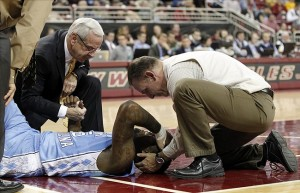 Jan 29, 2013; Chestnut Hill, Massachusetts, USA; A trainer and North Carolina Tar Heels head coach Roy Williams (left) holds the hand of guard P.J. Hairston (15) after he was injured during the first half against the Boston College Eagles at Conte Forum. Mandatory Credit: Greg M. Cooper-USA TODAY Sports