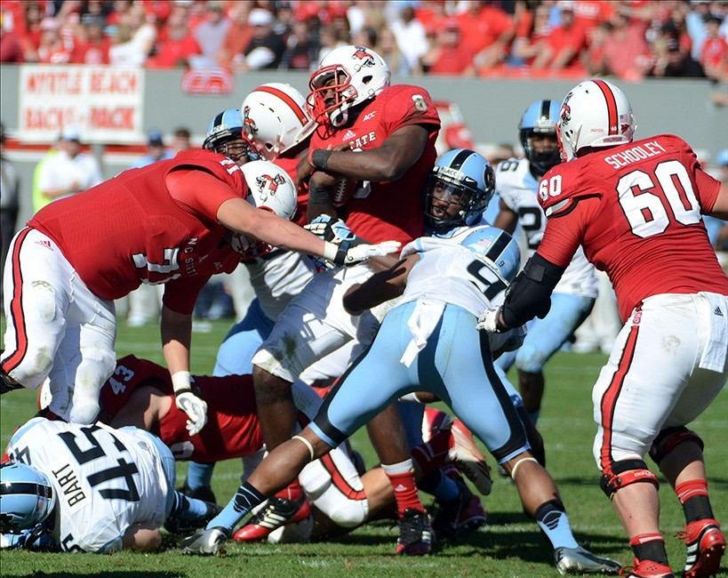 Nov 2, 2013; Raleigh, NC, USA; North Carolina State Wolfpack quarterback Brandon Mitchell (8) is tackled by North Carolina Tar Heels linebacker Travis Hughes (9) as he runs during the first half at Carter Finley Stadium. Mandatory Credit: Rob Kinnan-USA TODAY Sports