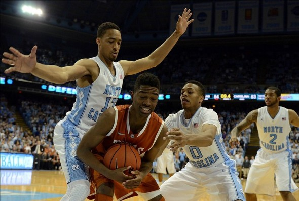 Dec 18, 2013; Chapel Hill, NC, USA; Texas Longhorns guard Isaiah Taylor (1) attempts to call timeout as he is pressured by North Carolina Tar Heels forward J.P. Tokoto (13) and guard Nate Britt (0) during the second half at the Dean E. Smith Student Activities Center. Texas won 86-83. Mandatory Credit: Rob Kinnan-USA TODAY Sports