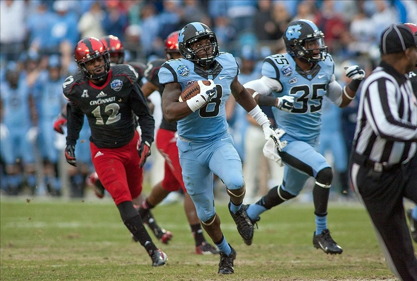 Dec 28, 2013; Charlotte, NC, USA; North Carolina Tar Heels running back T.J. Logan (8) returns a punt for a touchdown during the first quarter against the Cincinnati Bearcats at Bank of America Stadium. Mandatory Credit: Jeremy Brevard-USA TODAY Sports