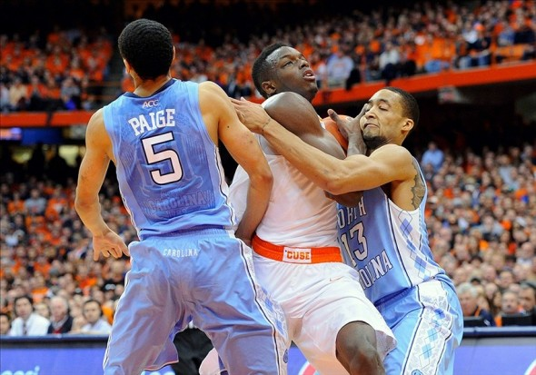Jan 11, 2014; Syracuse, NY, USA; Syracuse Orange forward Jerami Grant (center) gets tangled up with North Carolina Tar Heels forward J.P. Tokoto (right) and guard Marcus Paige (left) while driving to the basket during the first halfat the Carrier Dome. Mandatory Credit: Rich Barnes-USA TODAY Sports