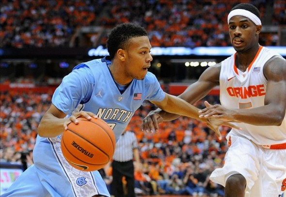 Jan 11, 2014; Syracuse, NY, USA; North Carolina Tar Heels guard Nate Britt (0) drives to the basket against the defense of Syracuse Orange forward C.J. Fair (5) during the second half at the Carrier Dome. Syracuse defeated North Carolina 57-45. Mandatory Credit: Rich Barnes-USA TODAY Sports