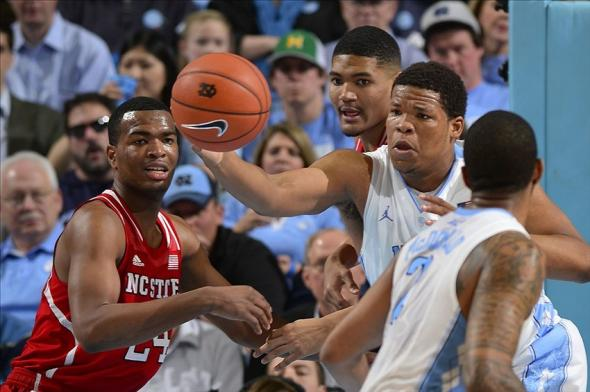 Feb 1, 2014; Chapel Hill, NC, USA; North Carolina State Wolfpack forwards T.J. Warren (24) and Kyle Washington (32) fight for the ball with North Carolina Tar Heels forward Kennedy Meeks (3) as guard Leslie McDonald (2) looks on in the second half. The Tar Heels defeated the Wolfpack 84-70 at Dean E. Smith Student Activities Center. Mandatory Credit: Bob Donnan-USA TODAY Sports