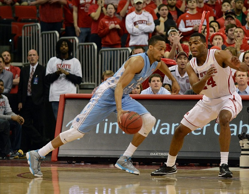 Feb 26, 2014; Raleigh, NC, USA; North Carolina Tar Heels forward J.P. Tokoto (13) dribbles around North Carolina State Wolfpack forward T.J. Warren (24)during the first half at PNC Arena. Mandatory Credit: Rob Kinnan-USA TODAY Sports