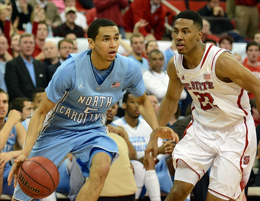 Feb 26, 2014; Raleigh, NC, USA; North Carolina Tar Heels guard Marcus Paige (5) moves past North Carolina State Wolfpack guard Ralston Turner (22)during the second half at PNC Arena. The Tarheels won 85-84 in overtime. Mandatory Credit: Rob Kinnan-USA TODAY Sports