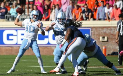 Oct 22, 2016; Charlottesville, VA, USA; North Carolina Tar Heels quarterback Mitch Trubisky (10) throws the ball as Virginia Cavaliers defensive tackle Donte Wilkins (1) chases in the first quarter at Scott Stadium. Mandatory Credit: Amber Searls-USA TODAY Sports