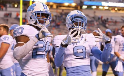 Oct 22, 2016; Charlottesville, VA, USA; North Carolina Tar Heels linebacker Dominique Ross (20) and Tar Heels defensive back K.J. Sails (9) celebrate after their game against the Virginia Cavaliers at Scott Stadium. The Tar Heels won 35-14. Mandatory Credit: Amber Searls-USA TODAY Sports