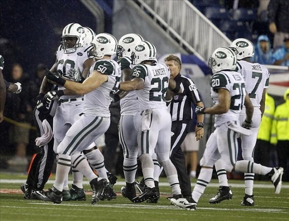 Sep 12, 2013; Foxboro, MA, USA; Referees and teammates grab New York Jets tackle D