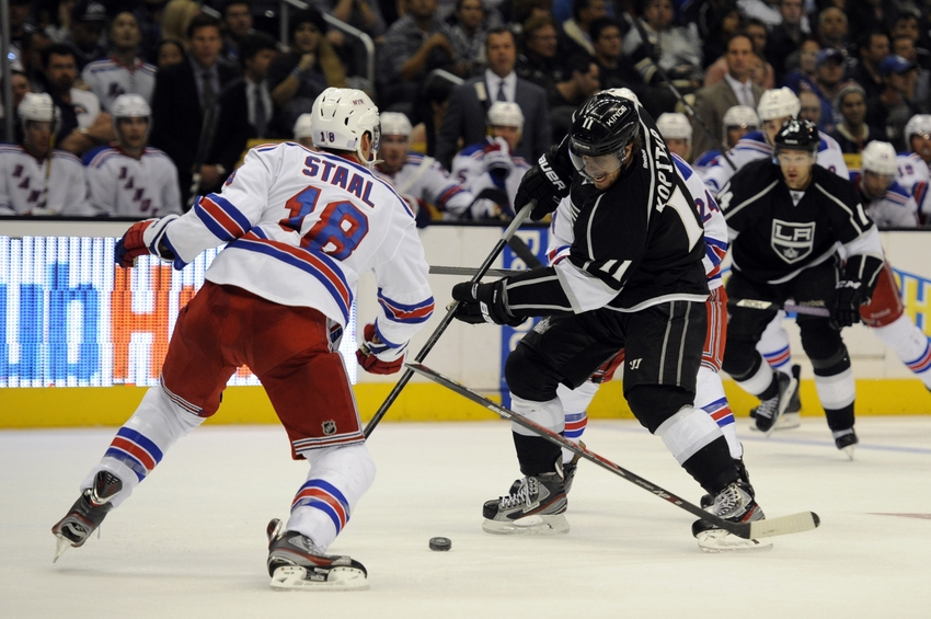 Oct 7, 2013; Los Angeles, CA, USA; Los Angeles Kings center Anze Kopitar (11) attempts to move the puck defended by New York Rangers defenseman Marc Staal (18) during the third period at Staples Center. The New York Rangers defeated the Los Angeles Kings 3-1. Mandatory Credit: Kelvin Kuo-USA TODAY Sports