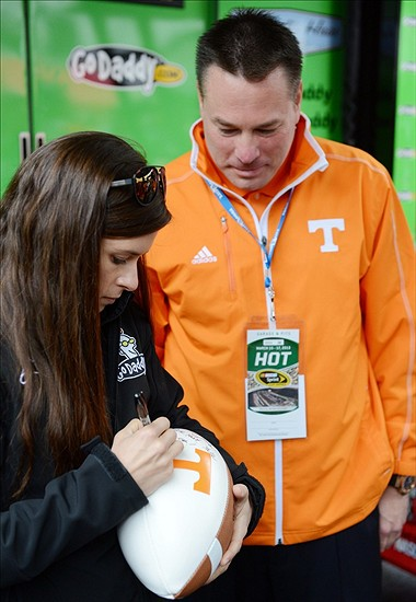 Mar 17, 2013; Bristol, TN, USA; NASCAR Sprint Cup Series driver Danica Patrick (left) autographs a football for Tennessee Volunteers head football coach Butch Jones before the Food City 500 at Bristol Motor Speedway. Mandatory Credit: Randy Sartin-USA TODAY Sports