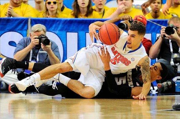 Mar 14, 2014; Atlanta, GA, USA; Florida Gators guard Scottie Wilbekin (5) and Missouri Tigers guard Jordan Clarkson (5) battle for the ball on the floor during the second half in the quarterfinals of the SEC college basketball tournament at Georgia Dome. Florida defeated Missouri 72-49. Mandatory Credit: Dale Zanine-USA TODAY Sports