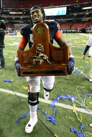 Dec 7, 2013; Atlanta, GA, USA; Auburn Tigers offensive linesman Avery Young (56) carries the trophy off the field after defeating the Missouri Tigers in the 2013 SEC Championship game at Georgia Dome. Auburn won 59-42. Mandatory Credit: John David Mercer-USA TODAY Sports