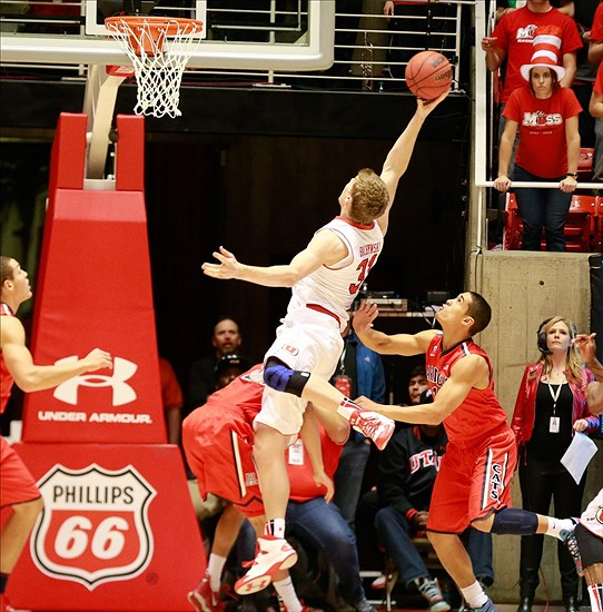 Feb 19, 2014; Salt Lake City, UT, USA Utah Utes center Dallin Bachynski (31) has his feet taken out from underneath of him during the first half against the Arizona Wildcats at Jon M. Huntsman Center. Mandatory Credit: Chris Nicoll-USA TODAY Sports