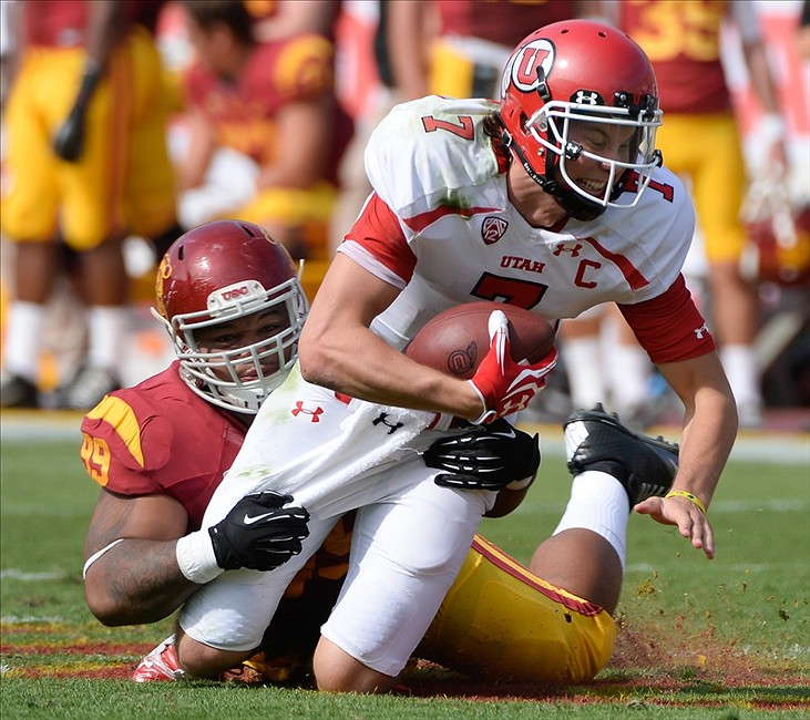 Oct 26, 2013; Los Angeles, CA, USA USC Trojans defensive tackle Antwaun Woods (99) sacks Utah Utes quarterback Travis Wilson (7) during first quarter action at Los Angeles Memorial Coliseum. Mandatory Credit: Robert Hanashiro-USA TODAY Sports