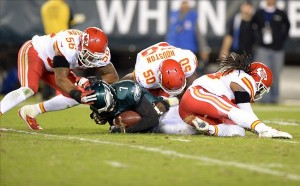 Sep 19, 2013; Philadelphia, PA, USA; Philadelphia Eagles quarterback Michael Vick (7) is tackled by Kansas City Chiefs players Derrick Johnson (56), Justin Houston (50) and Kendrick Lewis (23) at Lincoln Financial Field. The Chiefs defeated the Eagles 26-16. Mandatory Credit: Kirby Lee-USA TODAY Sports