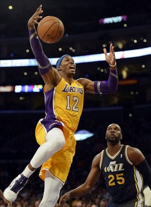 Jan 25, 2013; Los Angeles, CA, USA; Los Angeles Lakers center Dwight Howard (12) goes up to the basket as Utah Jazz center Al Jefferson (25) looks on during the first half at the Staples Center. Mandatory Credit: Richard Mackson-USA TODAY Sports