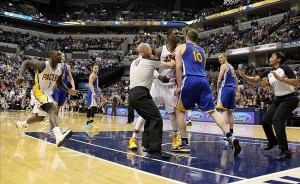 Feb 26 2013; Indianapolis, IN, USA; Officials try to separate a fight between Indiana Pacers center Roy Hibbert (55) and Golden State Warriors center David Lee (10) at Bankers Life Fieldhouse. Mandatory Credit: Brian Spurlock-USA TODAY Sports