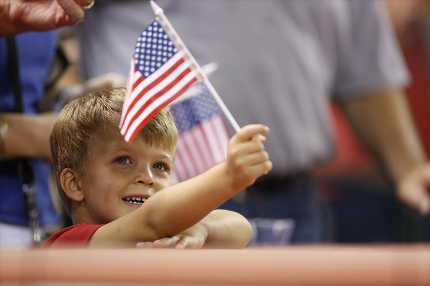 Sept 11, 2012; Houston, TX, USA; Three-year-old Lucas Kuznicki waves a flag during the playing of God Bless America on the 11th anniversary of the September 11th attacks in the seventh inning of the game between the Houston Astros and the Chicago Cubs at Minute Maid Park. Mandatory Credit: Thomas Campbell-USA TODAY Sports