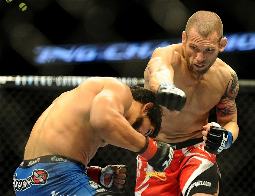 Feb 23, 2013; Anaheim, CA, USA; Matt Grice (blue gloves) punches Dennis Bermudez (red gloves) during their UFC featherweight bout at the Honda Center. Mandatory Credit: Jayne Kamin-Oncea-USA TODAY Sports