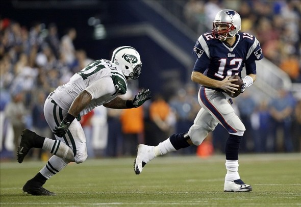 Sep 12, 2013; Foxborough, MA, USA; New England Patriots quarterback Tom Brady (12) scrambles away from New York Jets defensive end Sheldon Richardson (91) during the second quarter at Gillette Stadium. Mandatory Credit: Greg M. Cooper-USA TODAY Sports