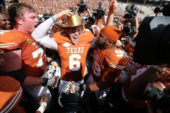 Oct 12, 2013; Dallas, TX, USA; Texas Longhorns quarterback Case McCoy (6) celebrates with the Golden Hat Trophy after the game against the Oklahoma Sooners during the Red River Rivalry at the Cotton Bowl Stadium. The Texas Longhorns beat the Oklahoma Sooners 36-20. Mandatory Credit: Matthew Emmons-USA TODAY Sports