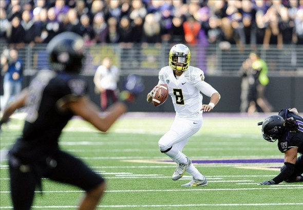 Oct 12, 2013; Seattle, WA, USA; Oregon Ducks quarterback Marcus Mariota (8) holds onto the ball during the game against the Washington Huskies at Husky Stadium. Oregon defeated Washington 45-24. Mandatory Credit: Steven Bisig-USA TODAY Sports