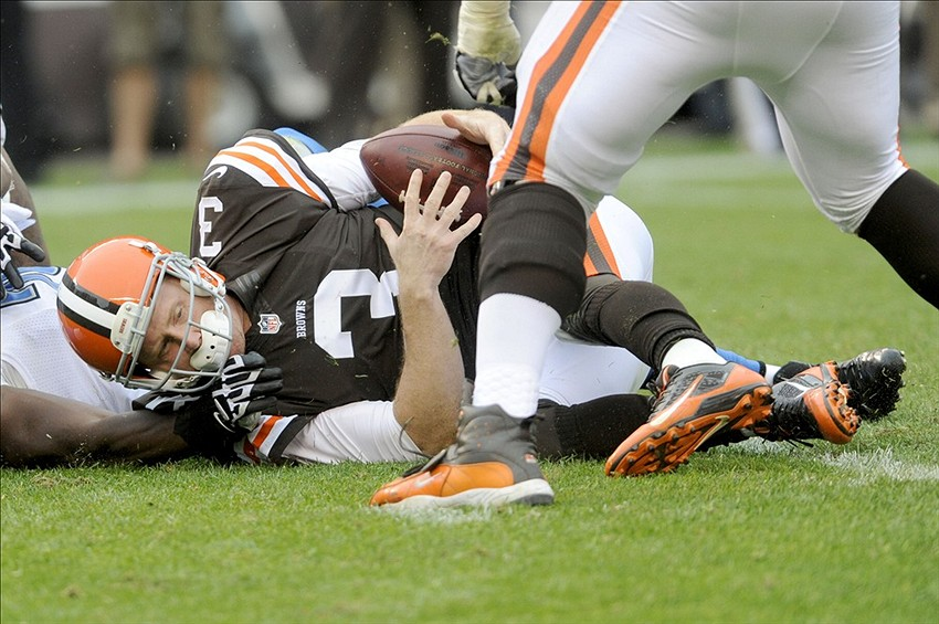 Oct 13, 2013; Cleveland, OH, USA; Cleveland Browns quarterback Brandon Weeden (3) is sacked by Detroit Lions defensive end Willie Young (79) during the third quarter at FirstEnergy Stadium. The Lions beat the Browns 31-17. Mandatory Credit: Ken Blaze-USA TODAY Sports