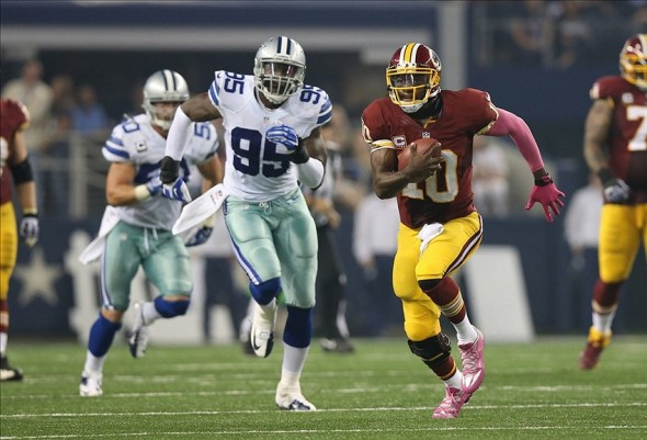 Oct 13, 2013; Arlington, TX, USA; Washington Redskins quarterback Robert Griffin III (10) runs with the ball in the third quarter against the Dallas Cowboys at AT&T Stadium