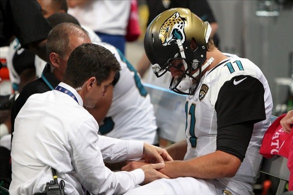Oct 6, 2013; St. Louis, MO, USA; A Jacksonville Jaguars trainer examines the left arm of quarterback Blaine Gabbert (11) during the first half against the St. Louis Rams at The Edward Jones Dome. Mandatory Credit: Scott Kane-USA TODAY Sports