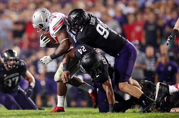 Oct 5, 2013; Evanston, IL, USA; Ohio State Buckeyes running back Carlos Hyde (34) is tackled by Northwestern Wildcats safety Ibraheim Campbell (24) and defensive lineman Dean Lowry (94) during the second quarter at Ryan Field. Mandatory Credit: Jerry Lai-USA TODAY Sports