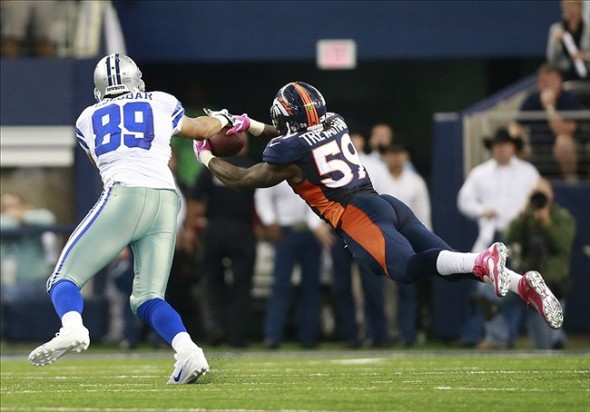 Oct 6, 2013; Arlington, TX, USA; Denver Broncos outside linebacker Danny Trevathan (59) intercepts a pass in front of Dallas Cowboys tight end Gavin Escobar (89) in the fourth quarter of the game at AT&T Stadium. Mandatory Photo Credit: USA Today Sports