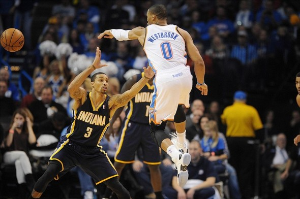 Dec 8, 2013; Oklahoma City, OK, USA; Oklahoma City Thunder point guard Russell Westbrook (0) passes the ball against Indiana Pacers point guard George Hill (3) during the third quarter at Chesapeake Energy Arena. Mandatory Credit: Mark D. Smith-USA TODAY Sports