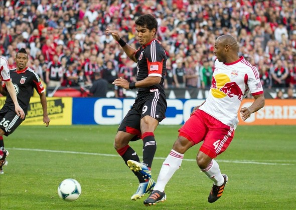 Apr 13, 2013; Washington, DC, USA; D.C. United forward Rafael Teixeira De Souza (9) takes a shot against New York Red Bulls defender Jamison Olave (4) during the first half at RFK Stadium. (Paul Frederiksen-USA TODAY Sports)