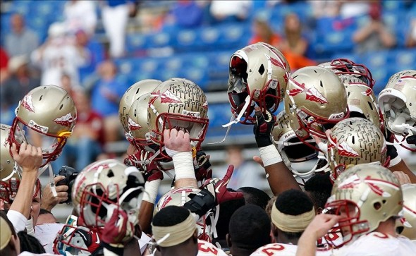 Nov 30, 2013; Gainesville, FL, USA; Florida State Seminoles hold up their helmets prior to the game against the Florida Gators at Ben Hill Griffin Stadium. Mandatory Credit: Kim Klement-USA TODAY Sports