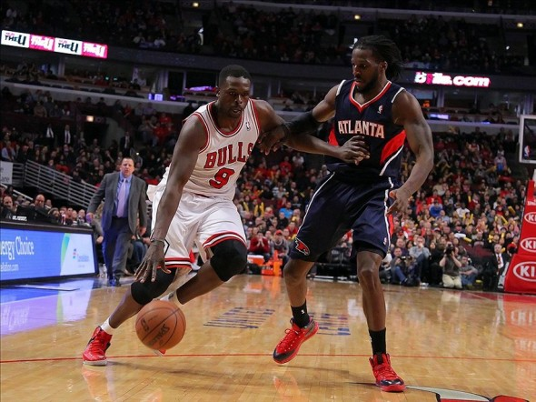 Jan 4, 2014; Chicago, IL, USA; Chicago Bulls small forward Luol Deng (9) drives against Atlanta Hawks small forward DeMarre Carroll (5) during the second half at the United Center. Chicago won 91-84. Mandatory Credit: Dennis Wierzbicki-USA TODAY Sports