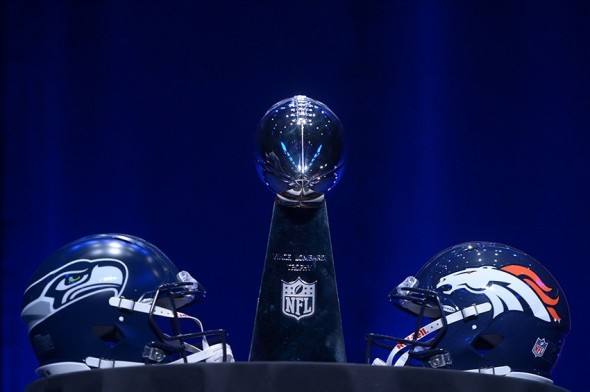 Jan 31, 2014; New York, NY, USA; Seattle Seahawks and Denver Broncos helmets are on display with the Vince Lombardi Trophy prior to a press conference at Rose Theater in advance of Super Bowl XLVIII. Mandatory Credit: Kirby Lee-USA TODAY Sports