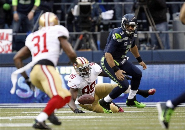 Jan 19, 2014; Seattle, WA, USA; Seattle Seahawks quarterback Russell Wilson (3) fumbles the ball after being hit by San Francisco 49ers outside linebacker Aldon Smith (99) during the first half of the 2013 NFC Championship football game at CenturyLink Field. Mandatory Credit: Joe Nicholson-USA TODAY Sports