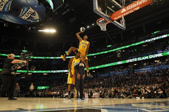 Feb 25, 2012; Orlando, FL, USA; Paul George of the Indiana Pacers completes a dunk as he jumps over Roy Hibbert and Dahntay Jones at the 2012 NBA All-Star Slam Dunk Contest at the Amway Center. Mandatory Credit: Bob Donnan-USA TODAY Sports
