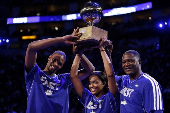 Feb 16, 2013; Houston, TX, USA; Miami Heat player Chris Bosh (left) hoists the shooting stars trophy with Chicago Sky player Swin Cash (middle) and Atlanta Hawks former player Dominique Wilkins (right) after the 2013 NBA all star shooting stars competition at the Toyota Center. Mandatory Credit: Brett Davis-USA TODAY Sports