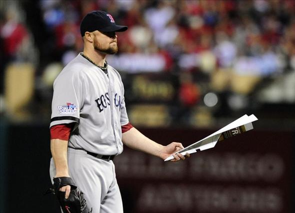 Oct 28, 2013; St. Louis, MO, USA; Boston Red Sox starting pitcher Jon Lester (31) picks up a paper airplane that was thrown on the field during the seventh inning of game five of the MLB baseball World Series against the St. Louis Cardinals at Busch Stadium. Mandatory Credit: Jeff Curry-USA TODAY Sports