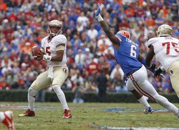 Nov 30, 2013; Gainesville, FL, USA; Florida State Seminoles quarterback Jameis Winston (5) drops back as Florida Gators defensive end Dante Fowler Jr. (6) defends during the first quarter at Ben Hill Griffin Stadium. Mandatory Credit: Kim Klement-USA TODAY Sports