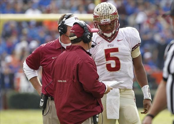 Nov 30, 2013; Gainesville, FL, USA; Florida State Seminoles head coach Jimbo Fisher talks with quarterback Jameis Winston (5) against the Florida Gators during the second half at Ben Hill Griffin Stadium. Florida State Seminoles defeated the Florida Gators 37-7. Mandatory Credit: Kim Klement-USA TODAY Sports